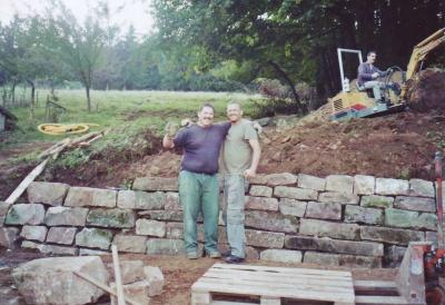 Two good friends pose for a photo in front of the home-made wall