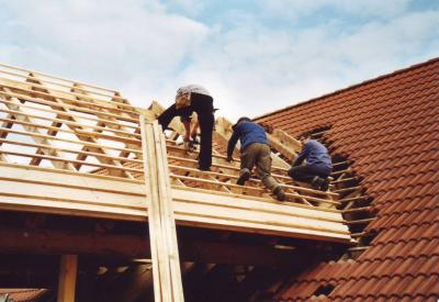 Workers attach wooden slats on the roof